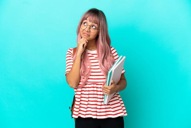 Jeune étudiante aux cheveux roses isolée sur fond bleu et levant