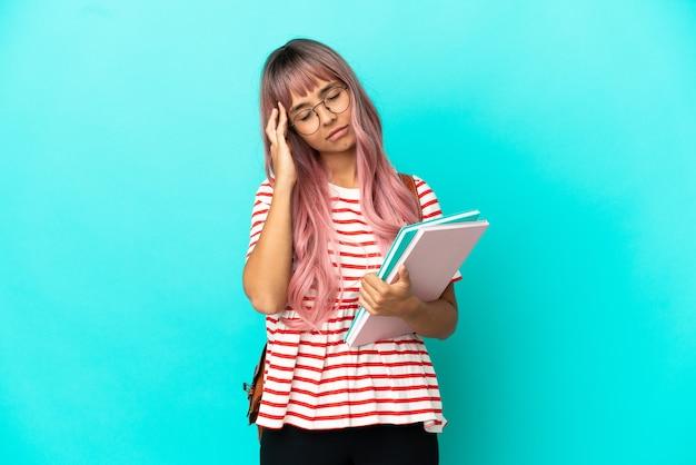 Jeune étudiante aux cheveux roses isolée sur fond bleu avec maux de tête