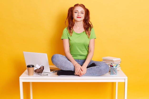 Jeune étudiante aux cheveux rouges assis sur un tableau blanc avec les jambes croisées, drôle de dame avec des queues de cheval, regardant la caméra