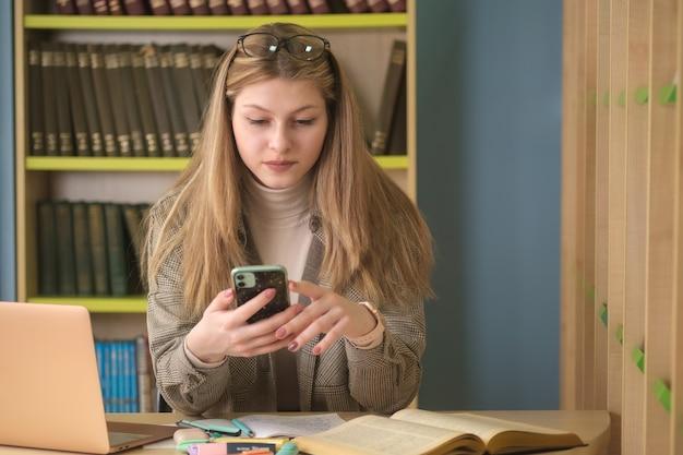 Jeune étudiante belle fille travaille avec des livres dans la bibliothèque. préparation aux examens à la bibliothèque