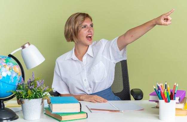 Jeune étudiante blonde excitée assise au bureau avec des outils scolaires gardant la main sur le bureau regardant et pointant sur le côté isolé sur un mur vert olive