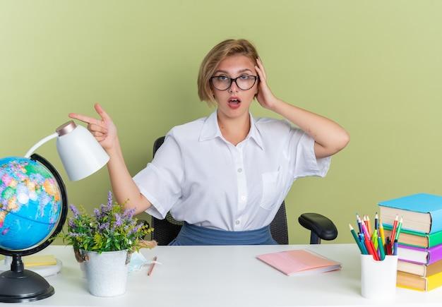 Jeune étudiante blonde inquiète portant des lunettes assise au bureau avec des outils scolaires en gardant la main sur la tête en regardant la caméra pointant sur le côté isolé sur un mur vert olive