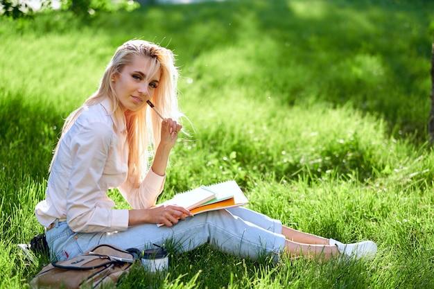 Jeune étudiante blonde avec un livre, un cahier et un stylo sur le pré. préparation de la session et des examens. portrait en plein air