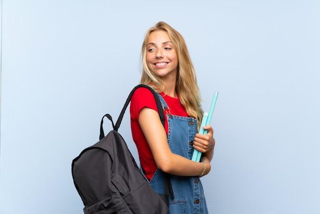 Jeune étudiante blonde sur mur bleu isolé en riant
