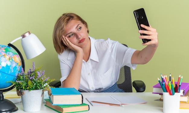Jeune étudiante blonde sérieuse assise au bureau avec des outils scolaires en gardant la main sur le visage en prenant un selfie isolé sur un mur vert olive
