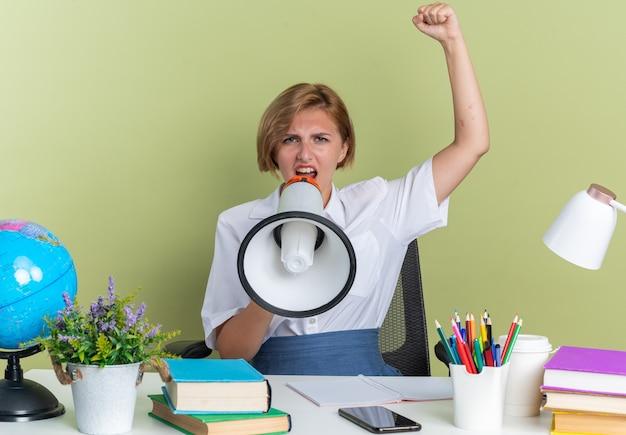 Jeune étudiante blonde stricte assise au bureau avec des outils scolaires parlant par le haut-parleur regardant la caméra levant le poing isolé sur un mur vert olive