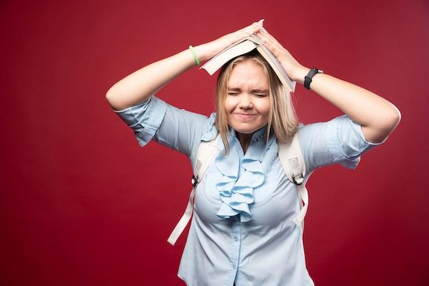 Une jeune étudiante blonde tient son livre à la tête et a l'air fatiguée et confuse.