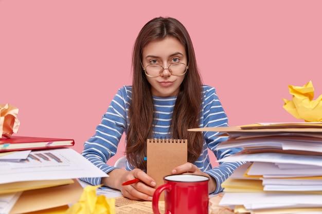 Jeune étudiante brune assise au bureau avec des livres