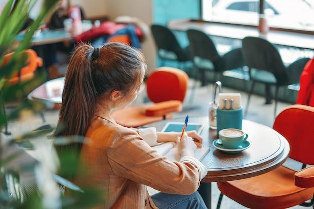 Jeune étudiante brune à faire ses devoirs dans un ordinateur portable avec du café au café