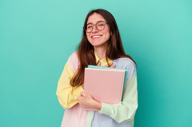 Jeune étudiante caucasienne éclate de rire en gardant la main sur la poitrine.