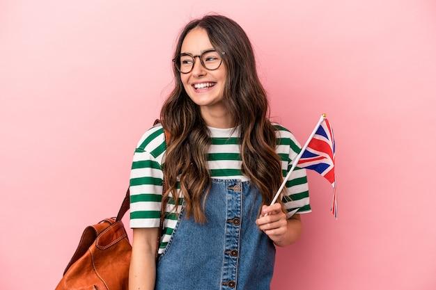Jeune étudiante caucasienne étudiant l'anglais isolée sur fond rose regarde de côté souriante, gaie et agréable.