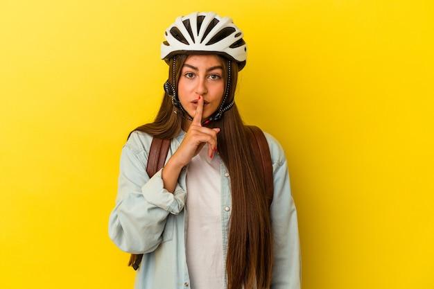 Jeune étudiante caucasienne portant un casque de vélo isolé sur fond jaune gardant un secret ou demandant le silence.