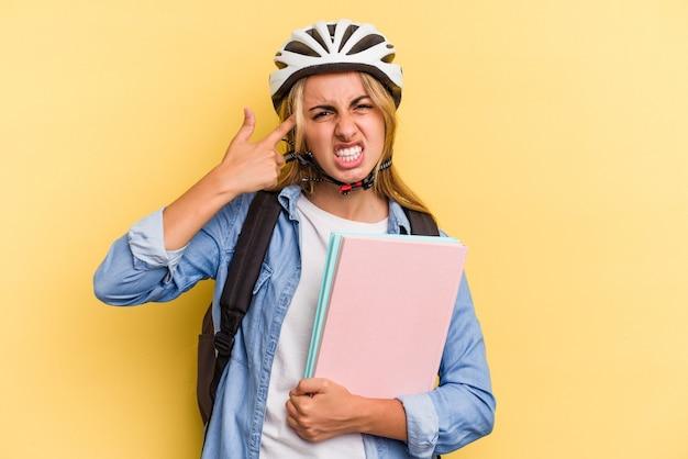 Jeune étudiante caucasienne portant un casque de vélo isolé sur fond jaune montrant un geste de déception avec l'index.