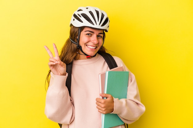 Jeune étudiante caucasienne portant un casque de vélo isolé sur fond jaune montrant le numéro deux avec les doigts.