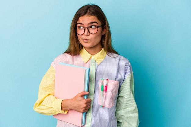Jeune étudiante caucasienne tenant des livres isolés sur fond bleu confus, se sent dubitative et incertaine.