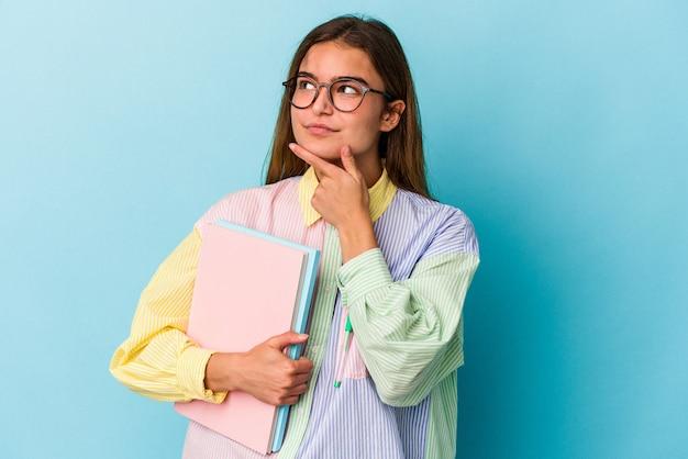 Jeune étudiante caucasienne tenant des livres isolés sur fond bleu regardant de côté avec une expression douteuse et sceptique.