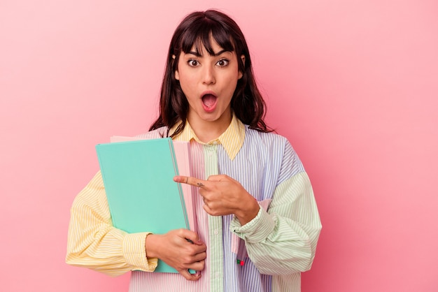 Jeune étudiante caucasienne tenant des livres isolés sur fond rose pointant vers le côté