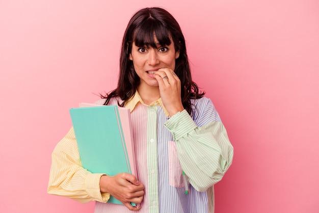 Jeune étudiante caucasienne tenant des livres isolés sur fond rose, se ronger les ongles, nerveux et très anxieux.