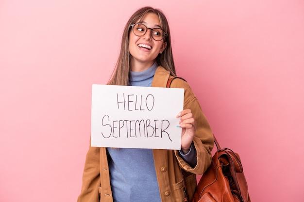 Une jeune étudiante caucasienne tenant une pancarte de septembre bonjour isolée sur fond rose regarde de côté souriante, gaie et agréable.