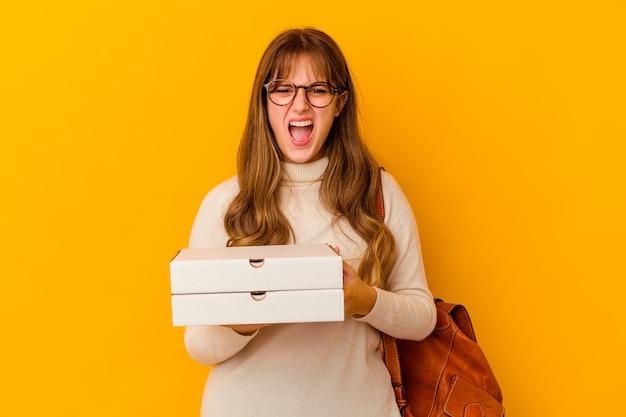 Jeune étudiante caucasienne tenant des pizzas sur fond isolé criant très en colère et agressif.