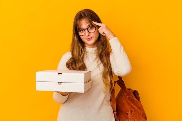 Jeune étudiante caucasienne tenant des pizzas sur fond isolé, pointant le temple avec le doigt, pensant, concentré sur une tâche.