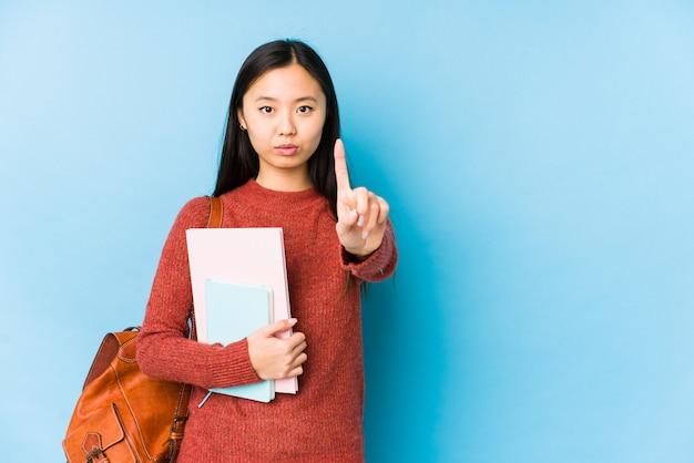 Jeune étudiante chinoise femme isolée montrant le numéro un avec le doigt.