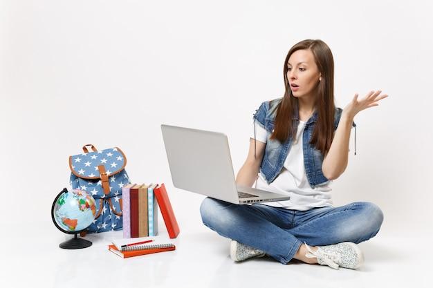 Jeune étudiante choquée tenant à l'aide d'un ordinateur portable écartant la main assise près du sac à dos globe, livres scolaires isolés