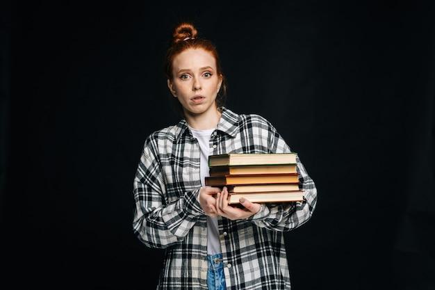 Jeune étudiante choquée tenant des livres et regardant la caméra sur fond noir