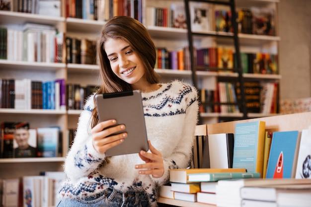 Jeune étudiante ciblée à l'aide d'un ordinateur tablette dans une bibliothèque
