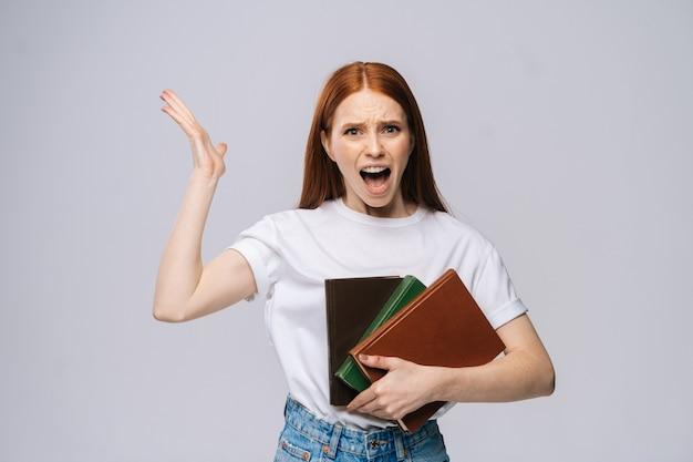 Jeune étudiante en colère tenant un livre et criant en regardant la caméra