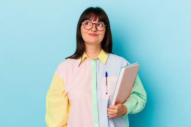 Jeune étudiante curvy woman holding books isolés sur fond bleu rêvant d'atteindre des objectifs et des buts