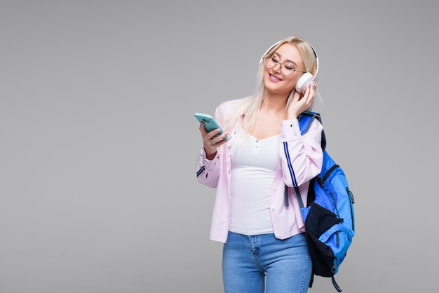 Jeune étudiante dans les écouteurs avec sac à dos, boire du café, souriant. démarrage, pigiste. apprentissage des langues étrangères en ligne, préparation aux examens