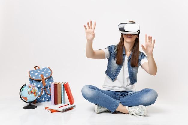 Une jeune étudiante dans des lunettes de réalité virtuelle touche quelque chose comme un bouton-poussoir, pointant vers un écran virtuel flottant près d'un livre d'école de sac à dos globe isolé sur un mur blanc