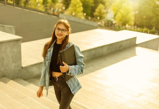 Une jeune étudiante dans une veste en jean et des lunettes monte les escaliers avec un ordinateur portable dans les mains dans la ville