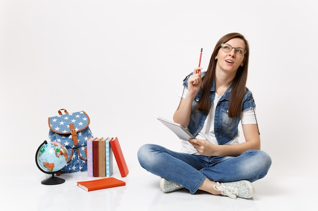 Jeune étudiante décontractée et intelligente se souvenant de réfléchir à la recherche d'un crayon pointant vers le haut près du sac à dos globe, livres scolaires isolés