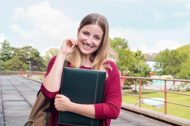 Jeune étudiante avec des dossiers sur le campus universitaire.