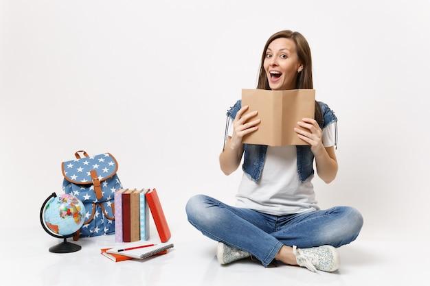 Jeune étudiante drôle surprise dans des vêtements en denim tenant un livre de lecture assis près du globe, sac à dos, livres scolaires isolés