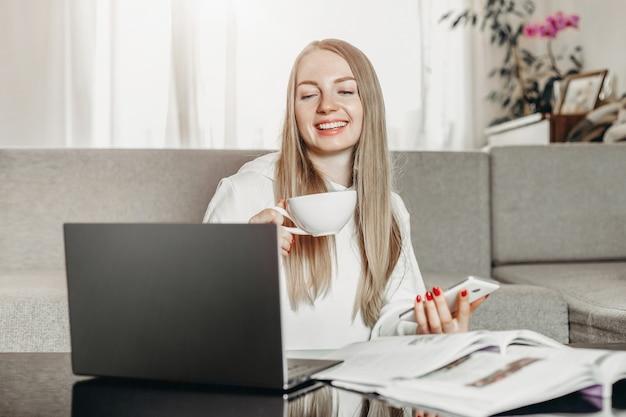 Une jeune étudiante est assise à la maison avec un ordinateur portable, un téléphone portable et des manuels et apprend l'anglais en ligne