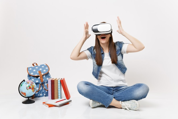 Jeune étudiante étonnée portant des lunettes de réalité virtuelle écartant les mains en s'asseyant près du globe, sac à dos, livres scolaires isolés sur mur blanc