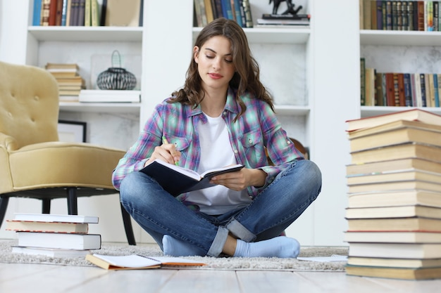 Jeune étudiante étudiant à la maison, écrivant un article pour publication, assise sur le sol contre un intérieur domestique confortable, entourée d'une pile de livres.