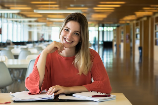Jeune étudiante étudie dans la bibliothèque.