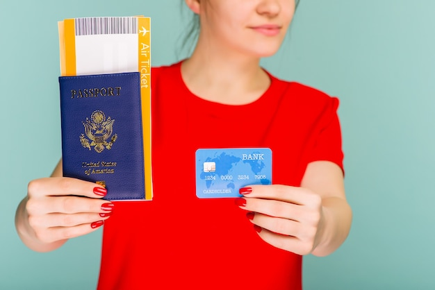 Jeune étudiante excitée souriante tenant un passeport et une carte de crédit