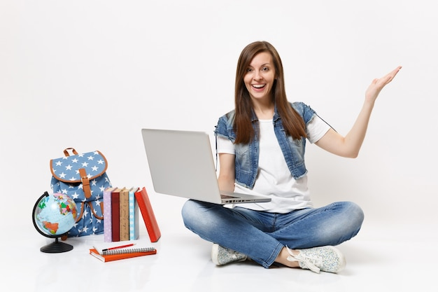 Jeune étudiante excitée tenant à l'aide d'un ordinateur portable écartant la main assise près du sac à dos globe, livres scolaires isolés sur mur blanc