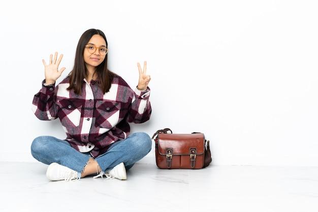Jeune étudiante femme assise sur le sol en comptant sept avec les doigts