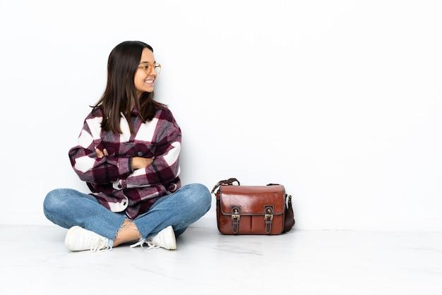 Jeune étudiante femme assise sur le sol en position latérale