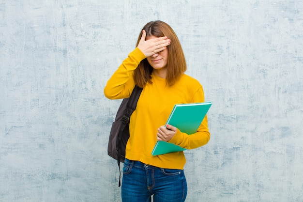 Jeune étudiante femme couvrant les yeux avec une main, se sentant effrayé ou anxieux, se demandant ou attendant aveuglément une surprise sur fond de mur de grunge