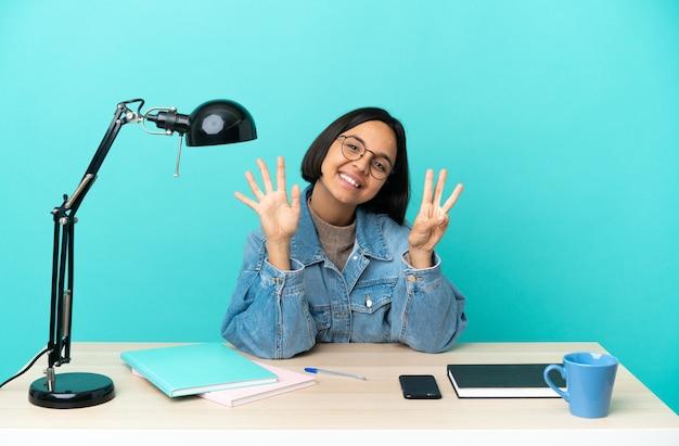 Jeune étudiante femme métisse étudiant sur une table comptant huit avec les doigts