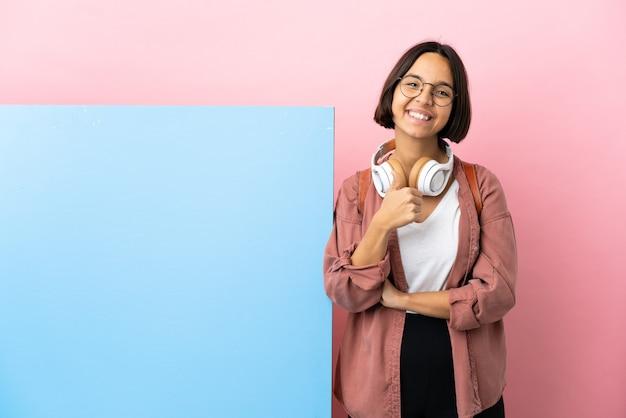 Jeune étudiante femme métisse avec une grande bannière sur fond isolé donnant un geste du pouce vers le haut