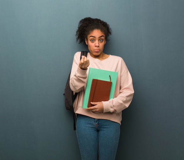 Jeune étudiante femme noire faisant un geste de besoin.
