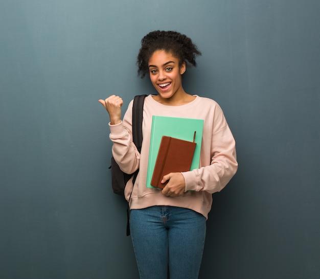 Jeune étudiante femme noire souriante et pointant vers le côté. elle tient des livres.